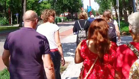 Bewoners lopen met de wethouder door de wijk na vernieuwen van de openbare ruimte