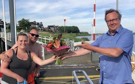 Bloemetje voor eerste passagier zomervaart pontje Vrevia